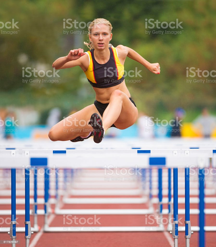 Front View of Beuatiful Young Women Racing 100m Hurdles stock photo