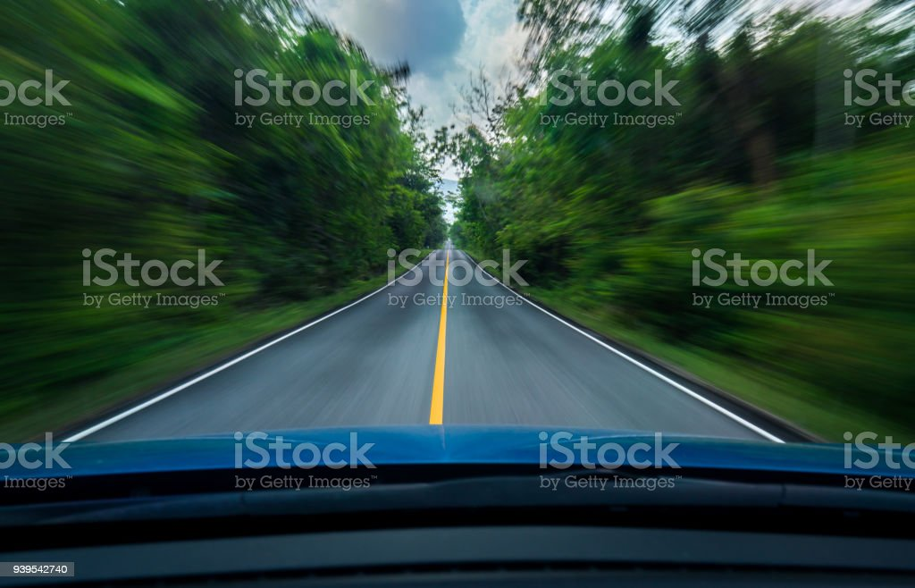 Front view of blue car driving with fast speed on the middle of asphalt road with white and yellow line of traffic symbol in the green forest. Trees beside the road is blurred. Car with blur motion. stock photo