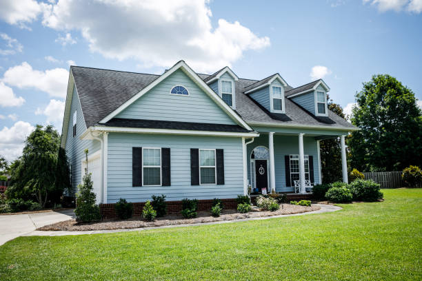Front View of blue house with siding in the suburbs pale blue house with siding on a large lot with traditional windows and shutters in a subdivision in the suburbs on a bright sunny blue sky day house exterior stock pictures, royalty-free photos & images
