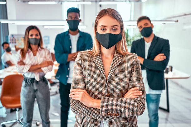 Front view of business people wearing protective masks in the office during the quarantine period stock photo