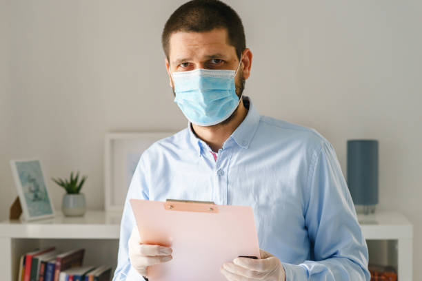 front view of caucasian man standing hold clipboard wearing medical protective mask to protect from virus bacteria pandemic disease while working from home quarantine or office looking to camera - businessman covid mask foto e immagini stock