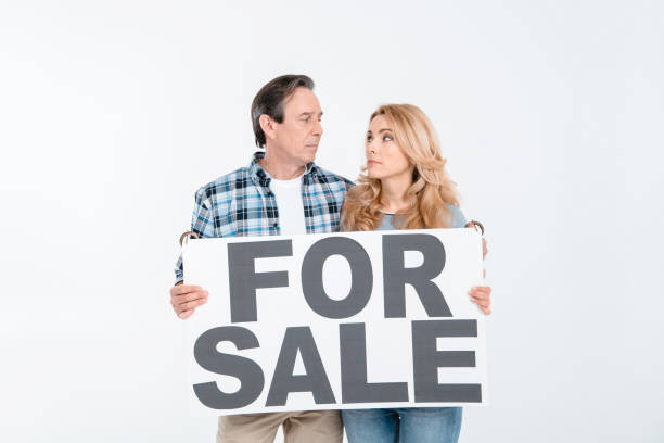 front view of couple holding card with words for sale on white stock