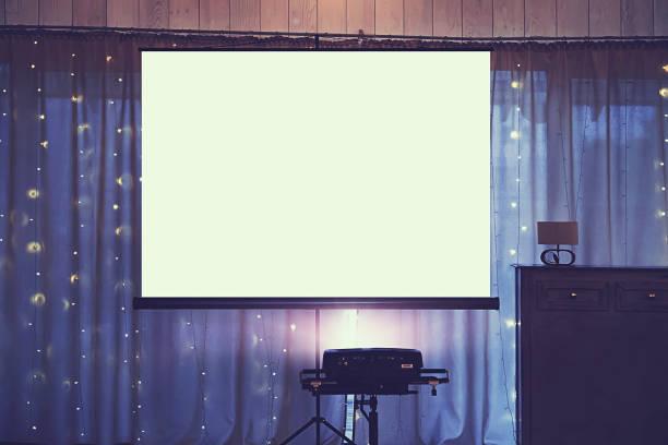 Vue de face de la salle de mariage décoré avec écran projecteur blanc vide au centre. Équipement de projection vidéo et diaporama à un événement festif. Salle de la banquette avec une planche pour la projection. - Photo