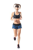 istock Front view of female jogger jogging and looking down. 854374092