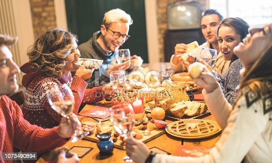 1064325668 istock photo Front view of friends group tasting christmas sweets food and having fun at home drinking champagne sparkling wine - Winter holidays concept with people enjoying time eating together - Warm filter 1073490894
