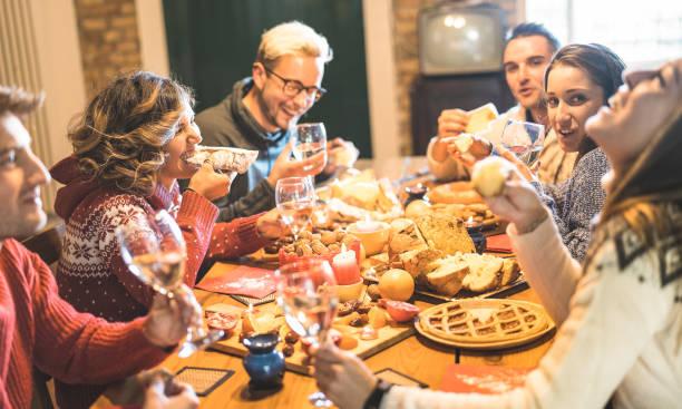 vue frontale du groupe amis dégustation alimentaire de bonbons de noël et de s'amuser à la maison de champagne mousseux - concept de vacances d'hiver avec des gens profitant de temps à manger ensemble - chaud filtre potable - diner entre amis photos et images de collection