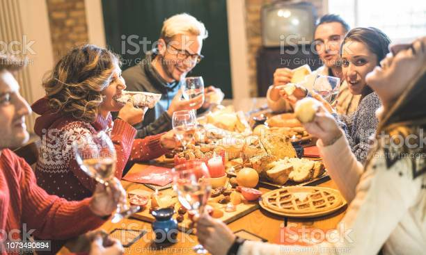Front View Of Friends Group Tasting Christmas Sweets Food And Having Fun At Home Drinking Champagne Sparkling Wine Winter Holidays Concept With People Enjoying Time Eating Together Warm Filter - Fotografie stock e altre immagini di Adulto