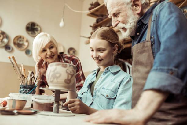 vorderansicht des mädchen malerei tontopf und großeltern helfen beim workshop - handbemalte teller stock-fotos und bilder