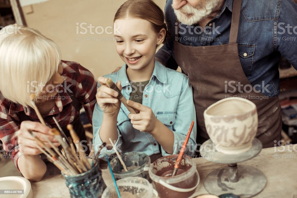 Front view of girl painting clay pot and grandparents helping at workshop stock photo