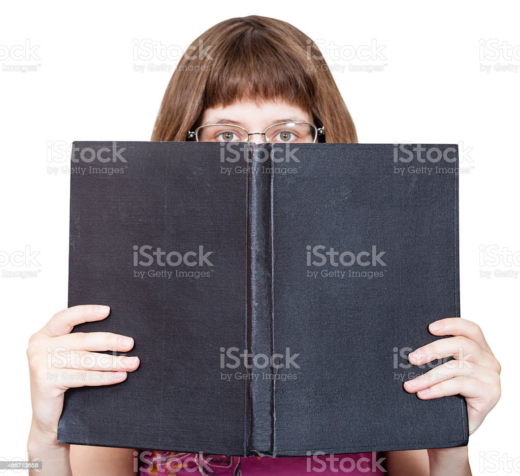 front view of girl with spectacles looks over book foto