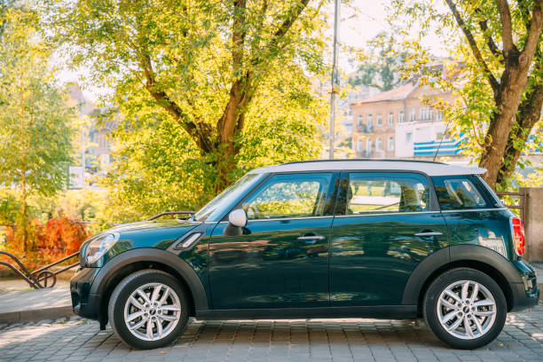 Front View Of Green Color Mini Cooper Car Parking At Street stock photo