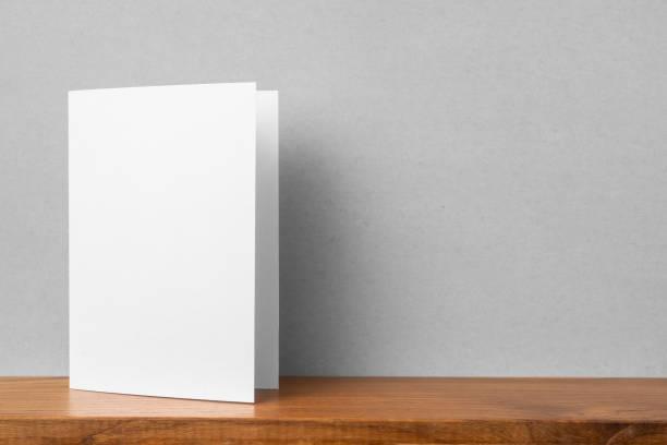 frontansicht der grußkarte auf bücherregal und grauer wand - druckerzeugnis stock-fotos und bilder
