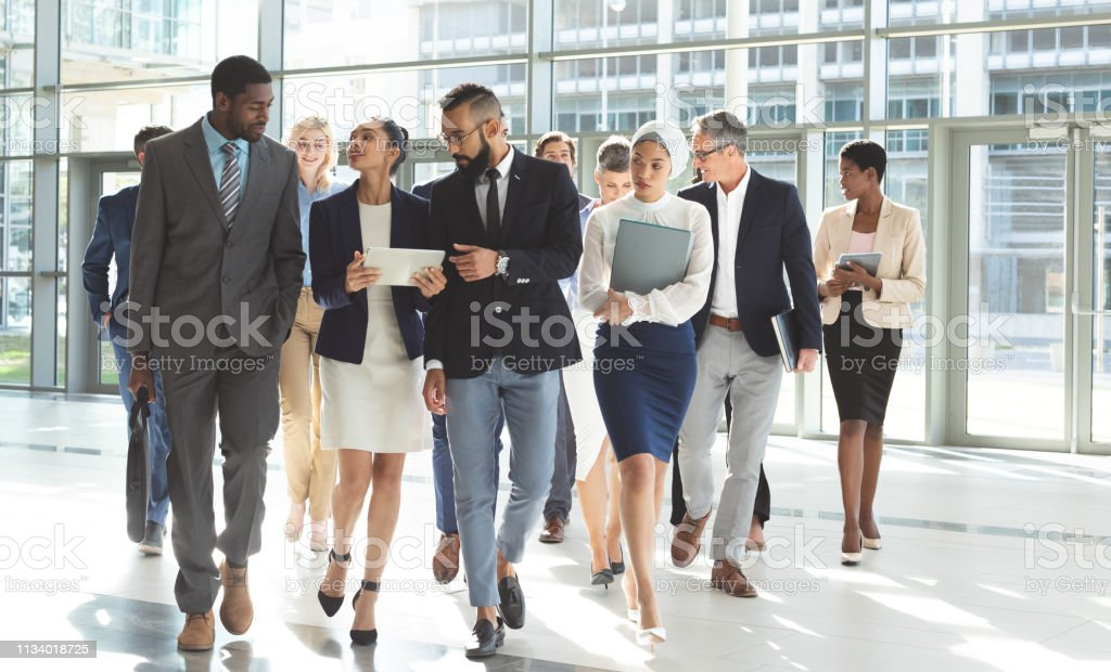 Front view of group of diverse business people walking together while...