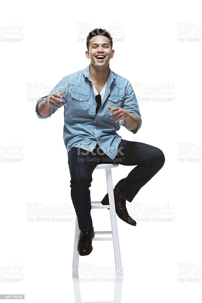 Front view of happy young man sitting on stool royalty-free stock photo