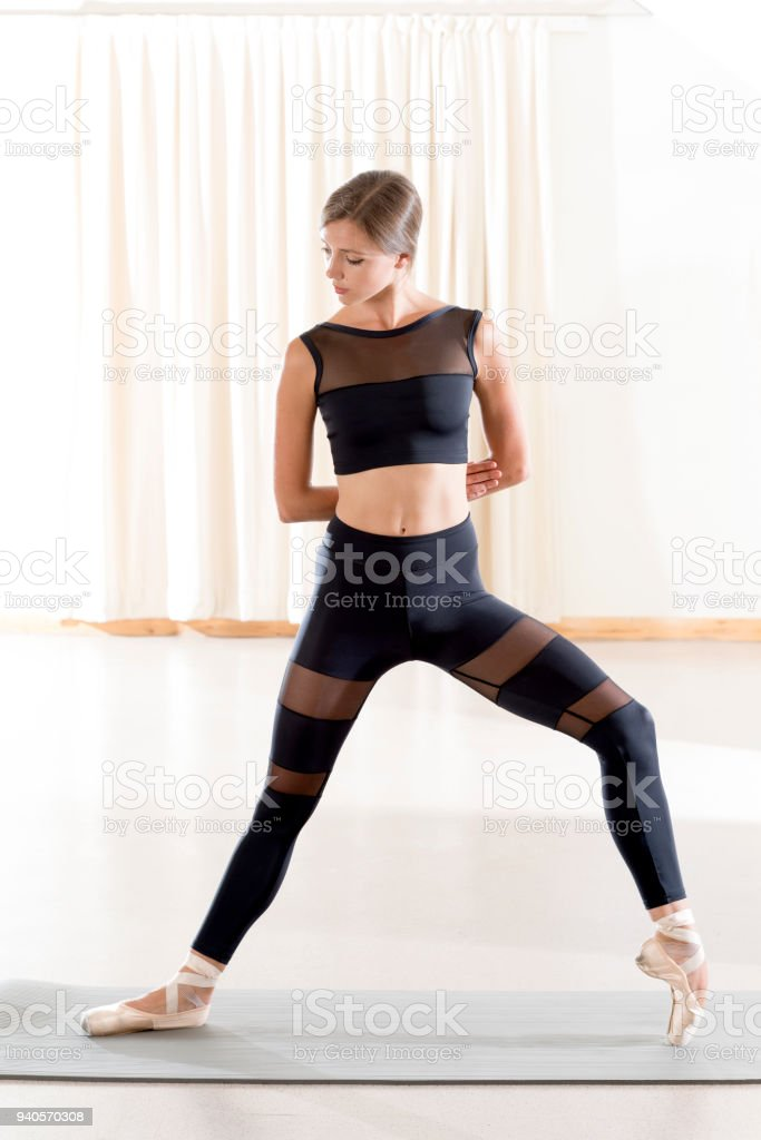 Front View of Lady Performing Standing Reversed Arm Shoulder Stretch stock photo
