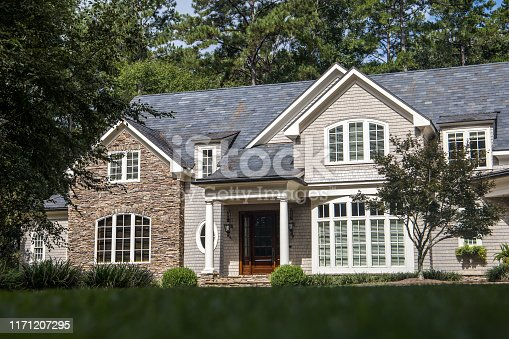 Front view of large estate home in the south with a gravel driveway and lots of windows. house made of brick, stone and clapboard in a cape cod style.