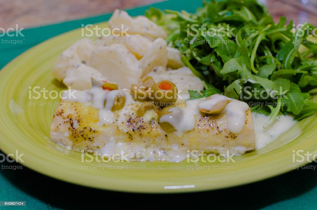 Front view of Mahi fish with potatoes and arugula stock photo