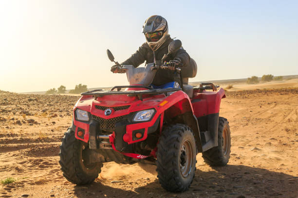 Front view of man riding buggy car in Ait Saoun moroccan desert Ait Saoun, Morocco - February 22, 2016: Man riding RZR 800 in Ait Saoun dessert in Morocco on a sunset evening. quadbike stock pictures, royalty-free photos & images