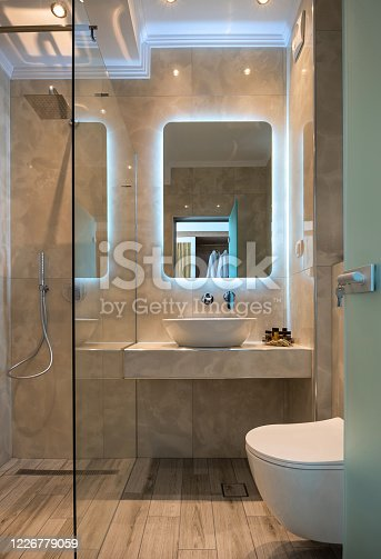 istock Front view of modern beige marble bathroom with vessel bowl sink, mirror back light, glass shower cabin, wall hung toilet, wooden floor 1226779059