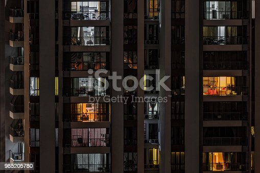 Background with night life in big city - front view of modern high-rise building with windows of cozy apartments in which light shines and people doing routine things. Malaysia, Cyberjaya.