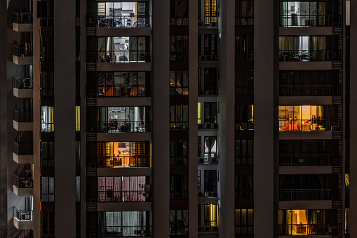 istock front view of modern high-rise building with windows of cozy apartments in which light shines and people doing routine things. 985205780