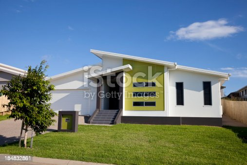 Front view of a new neat modern low set single story family home with green grass and blue sky. Click to see more...