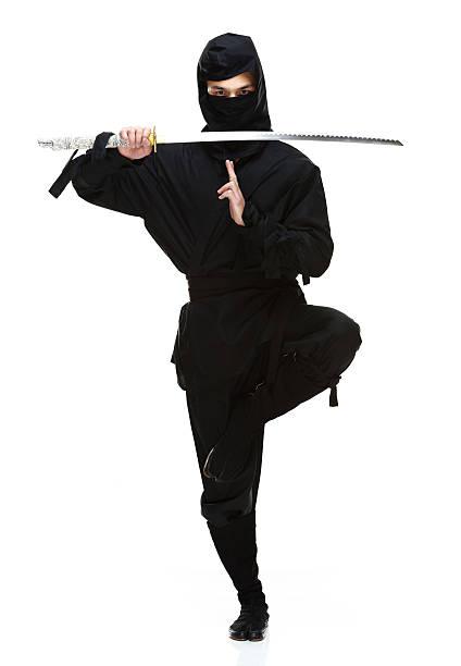 vista frontal de ninja en acción con espada - ninja fotografías e imágenes de stock