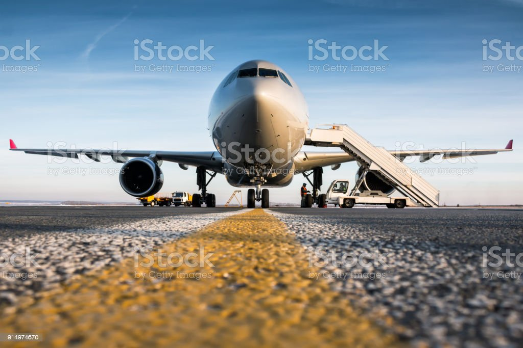 Front view of passenger airplane and boarding stairs at the airport apron стоковое фото
