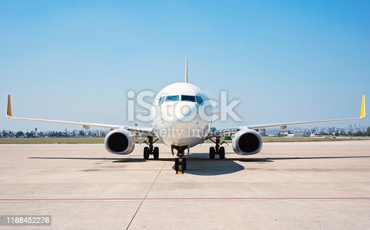 Front view of passenger airplane standing on runway.