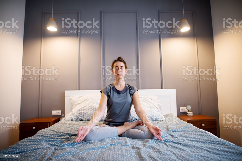 Front view of peaceful attractive middle aged active woman practising yoga on the bed holding eyes closed, sitting in Half Lotus exercise, Ardha Padmasana pose and wearing sportswear in the morning. stock photo