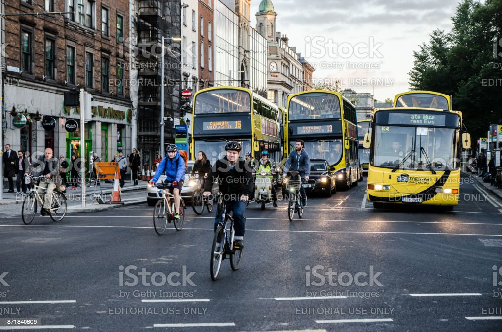 Front view of people riding bicycle in downtown O'Connell street of Dublin Ireland during rush hour a day of autumn stock photo