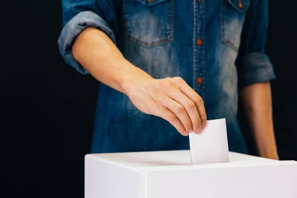 Frontansicht von Personen, die in einem Wahllokal Stimmzettel zur Wahlabgabe in schwarzem Hintergrund abgeben – Foto