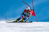 Young man compeeting at giant slalom race, bending the red gate, against the blue sky