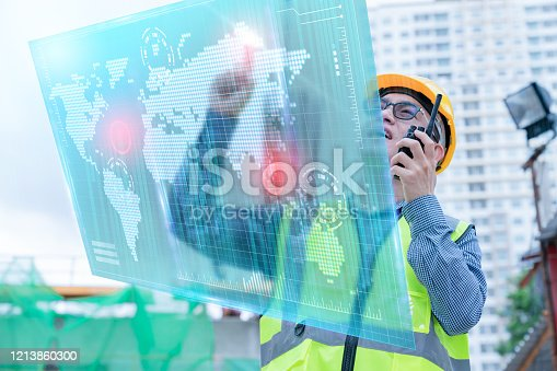 1136415363 istock photo front view of professional engineer asian male safety helmet manage control constuction site with expertise working with virtual monitor screen system control 1213860300