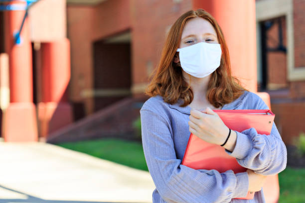 Front view of red-headed teen wearing mask on campus stock photo