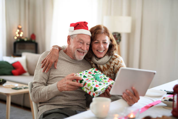 Front view of senior couple indoors at home at Christmas, having video call with family. stock photo