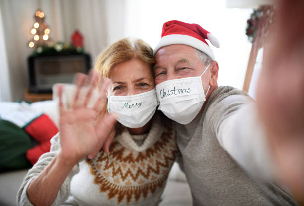 Front view of senior couple with face masks indoors at home at Christmas, taking selfie. stock photo