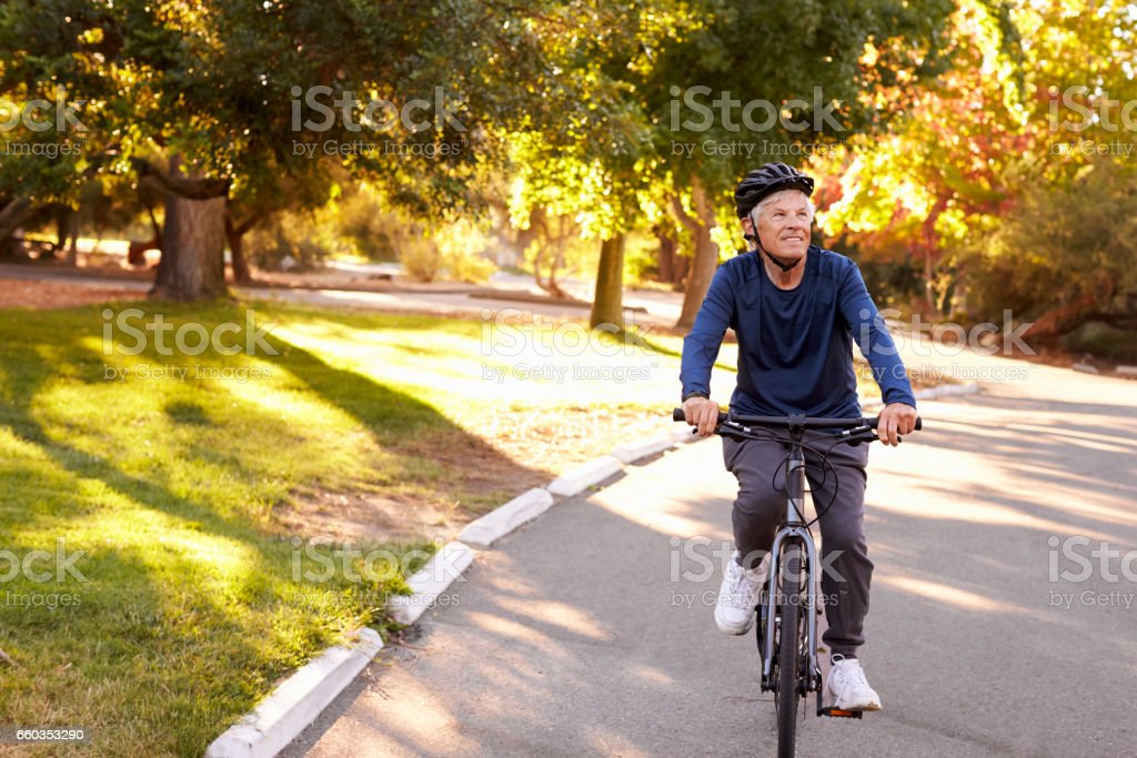Front View Of Senior Man Cycling Through Park stock photo