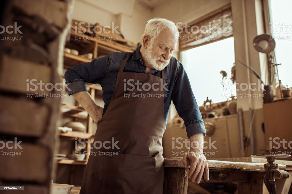 Front view of senior potter in apron standing and leaning on table against shelves with pottery goods at workshop foto de stock royalty-free