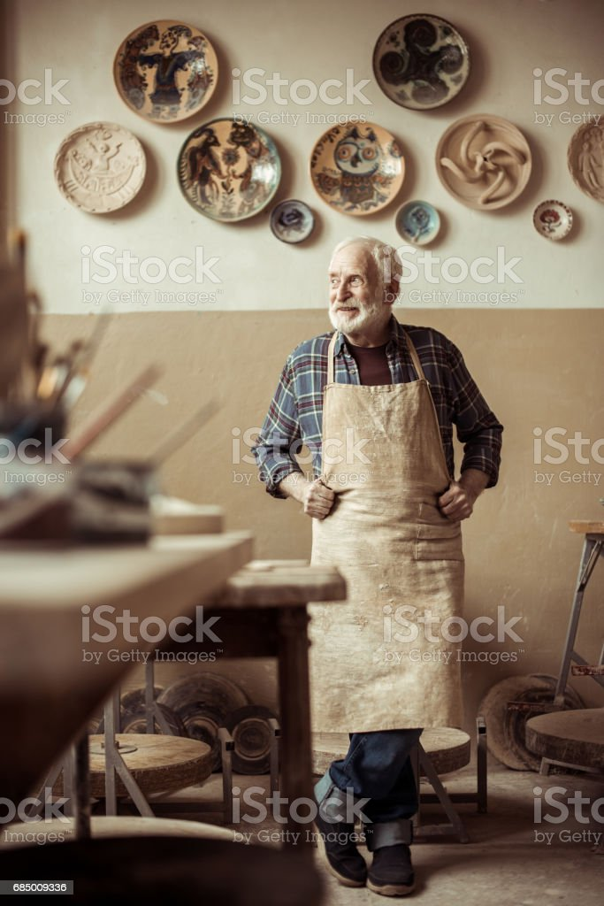 Front view of senior potter in apron standing at workshop Lizenzfreies stock-foto