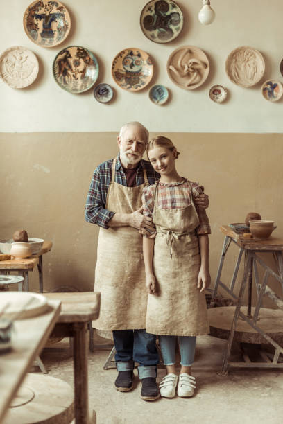 Front view of senior potter with his granddaughter in aprons standing at workshop stock photo