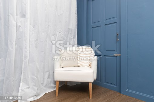 front view of single comfortable wooden leather chair with blue interior wall and white curtain.
