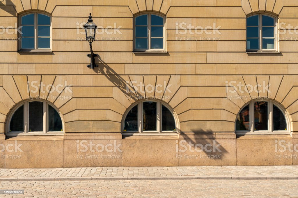 Front view of six arched windows on a old city building with stone wall. stock photo