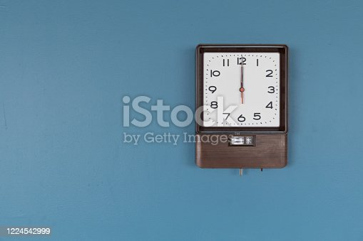 671883446 istock photo front view of square wooden wall clock with copy space on blue background 1224542999