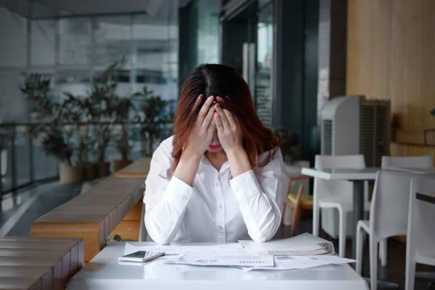 オフィスの机の上の手で顔を覆っているストレス イライラ若いアジア ビジネス女性の正面図 - 女性 落ち込む ストックフォトと画像