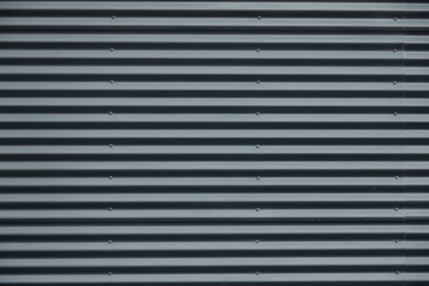 Front view of striped gray corrugated metal wall stock photo