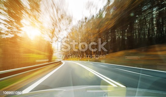 640042252 istock photo Front view of the highway road passing the country side inside the fast car long exposure shoot 1069651080