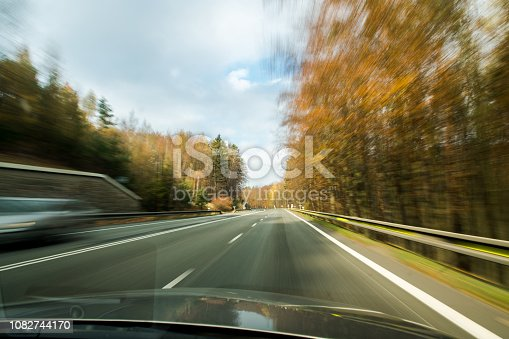 640042252 istock photo Front view of the highway road passing the country side inside the fast car long exposure shoot 1082744170