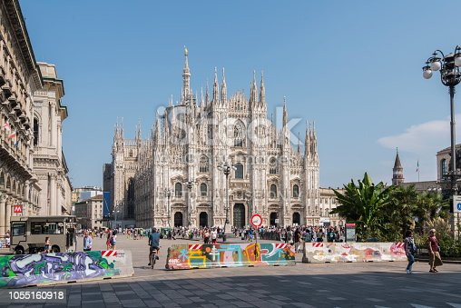 Front view of the Milan Cathedral (Duomo di Milanp) at Milan city, Italy and a lot of tourist walking around the square. Police barricades to ensure security are located at the entrance to the square. The construction of this gothic style cathedral began in 1386 and is visited daily by thousands of tourist.