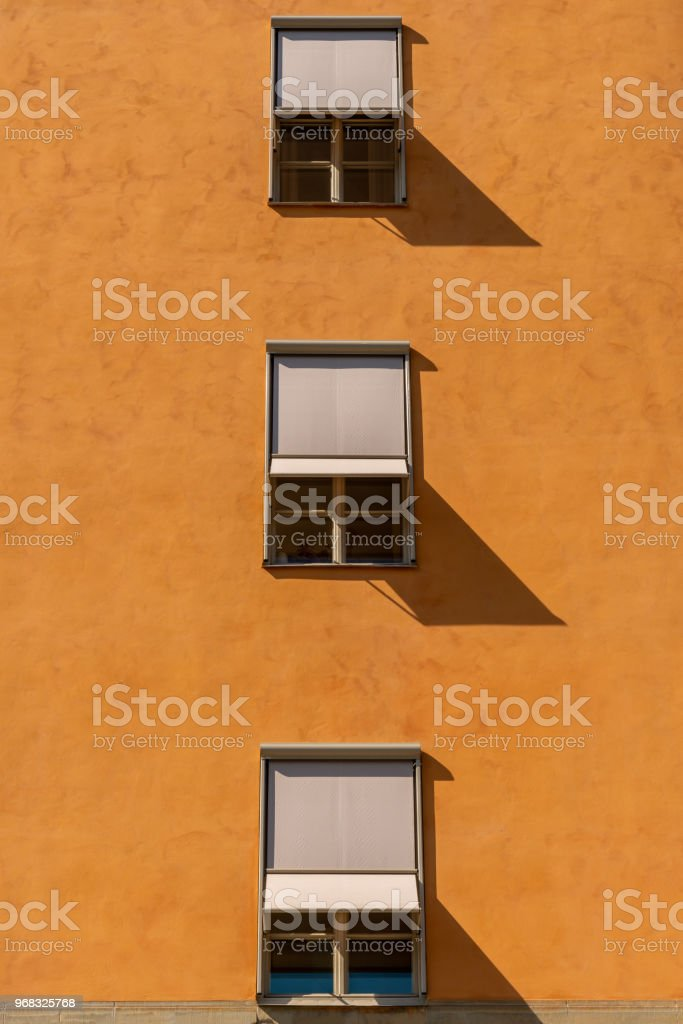 Front view of three symmetrical windows with sun blinds on a stone city building. stock photo